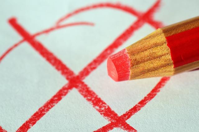 A red pencil casting a ballot