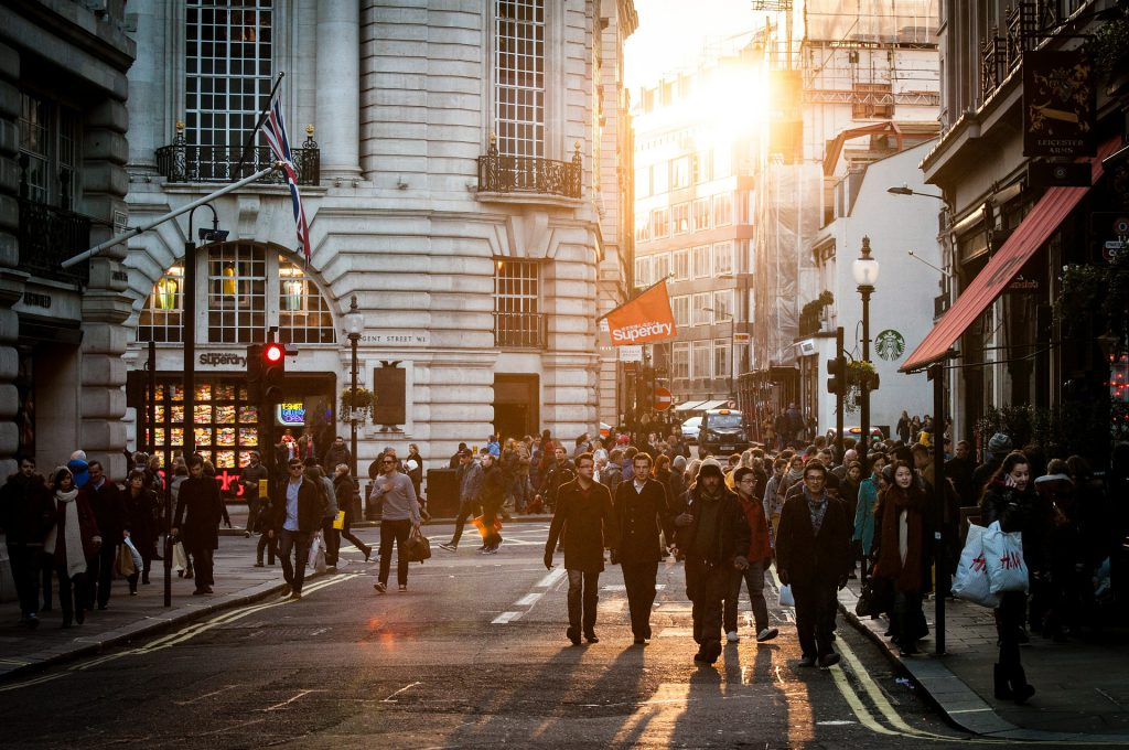 A crowd of shoppers stroll a busy high street as the sun glows beautifully behind them. How lovely.
