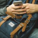 hands holding mobile phone rsting on backpack