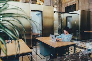 man sat at desk working on laptop